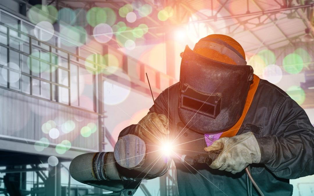 Welder wearing protective clothing